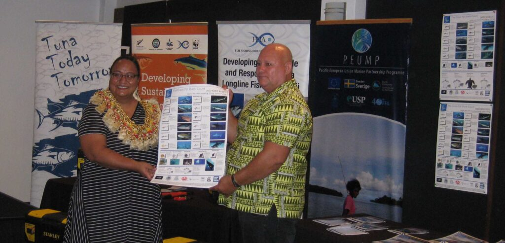 Ms Emma Christopher, Development Programme Coordinator from the New Zealand High Commission, presents Great Fiji Shark Count Shark, Ray and Turtle ID posters to Captain Charles Pickering  of the Fiji Fishing Industry Association